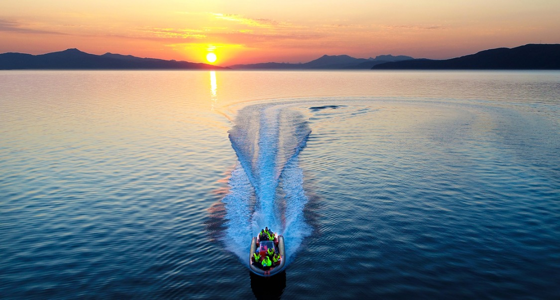 Gjeng fra Ofoten rør i båt på stille vann med solnedgang i bakgrunnen