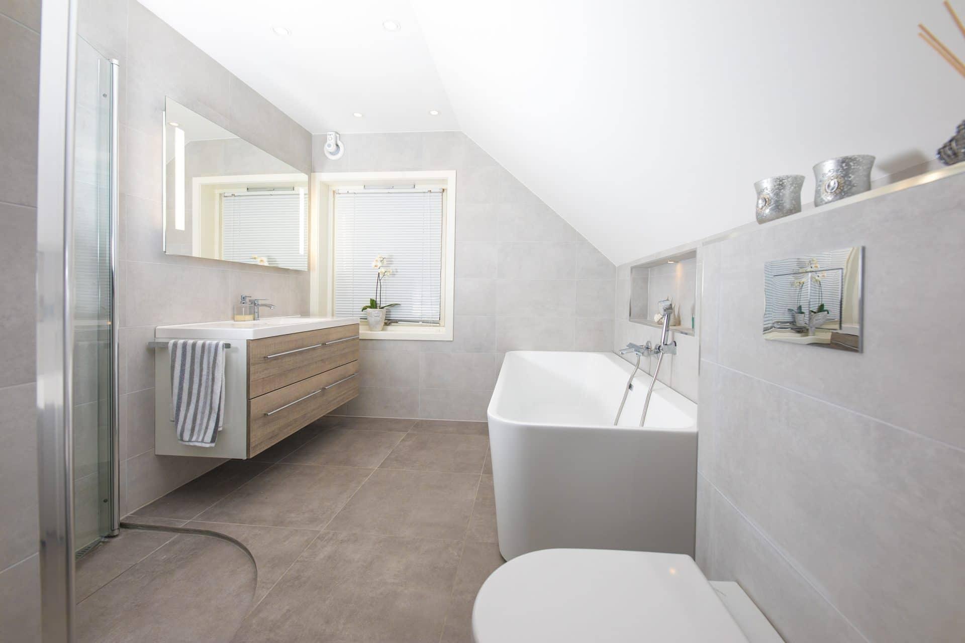Grått bad med badekar, dusjhjørne og vegghengt toalett