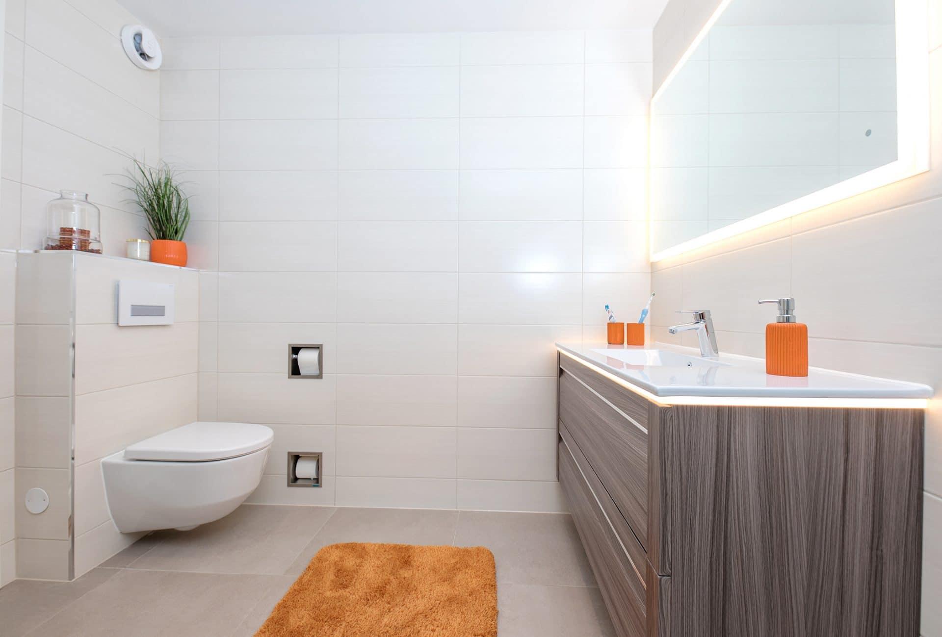 Nytt bad med hvite fliser og speil med lys