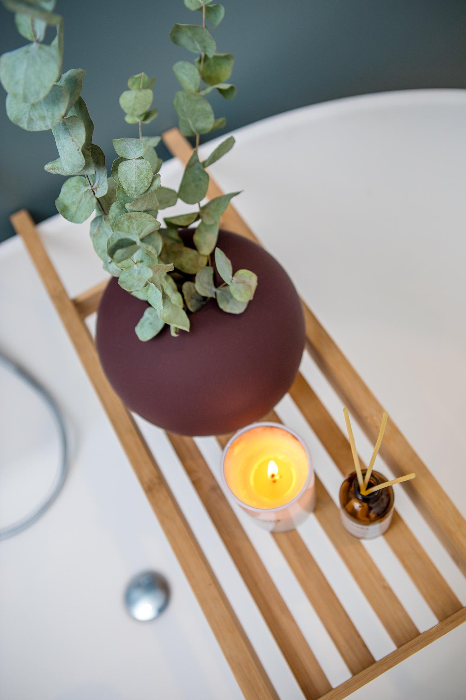 Detaljbilde av badekarbord med plante, duftlys og duftpinner