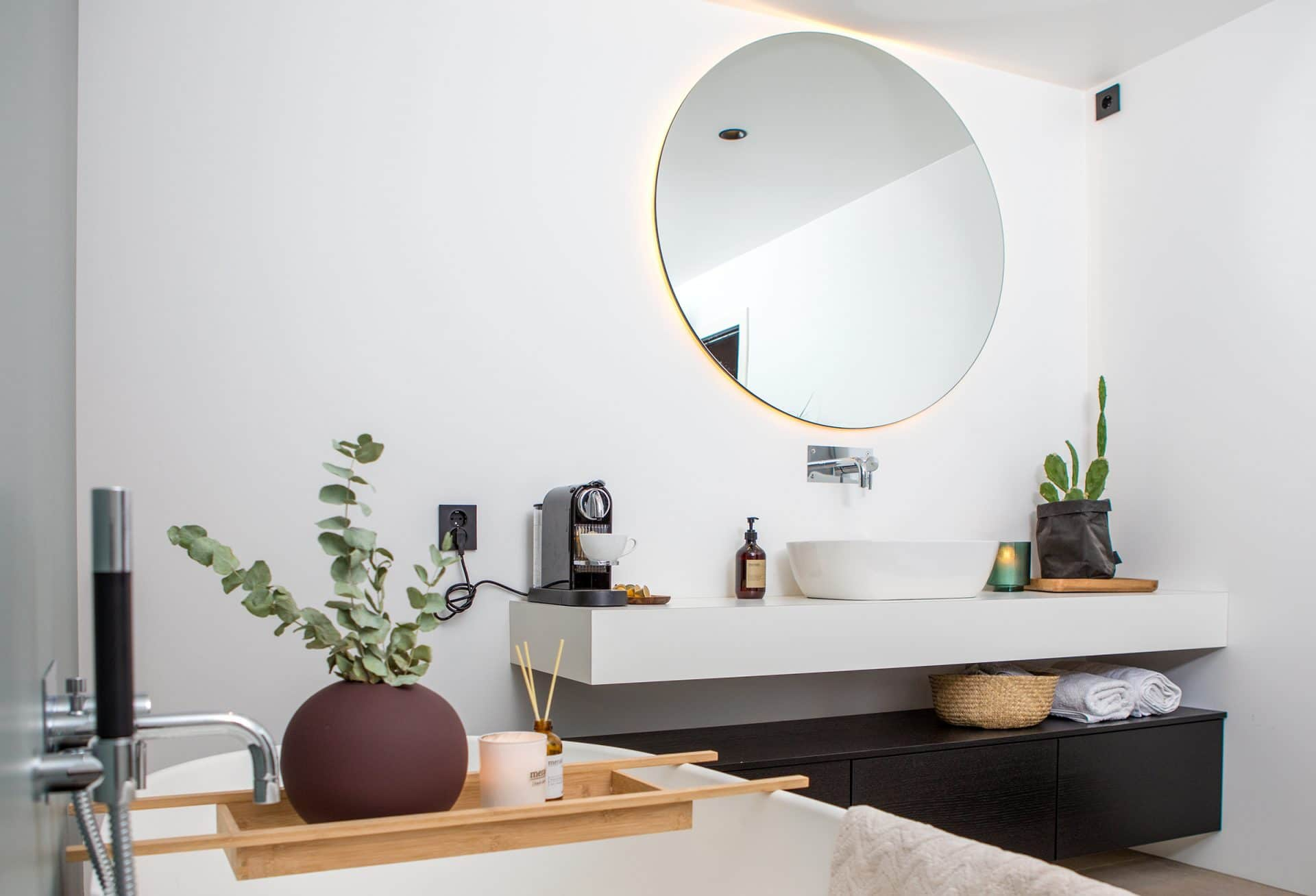 Detaljbilde fra bad med frittstående badekar og rundt speil