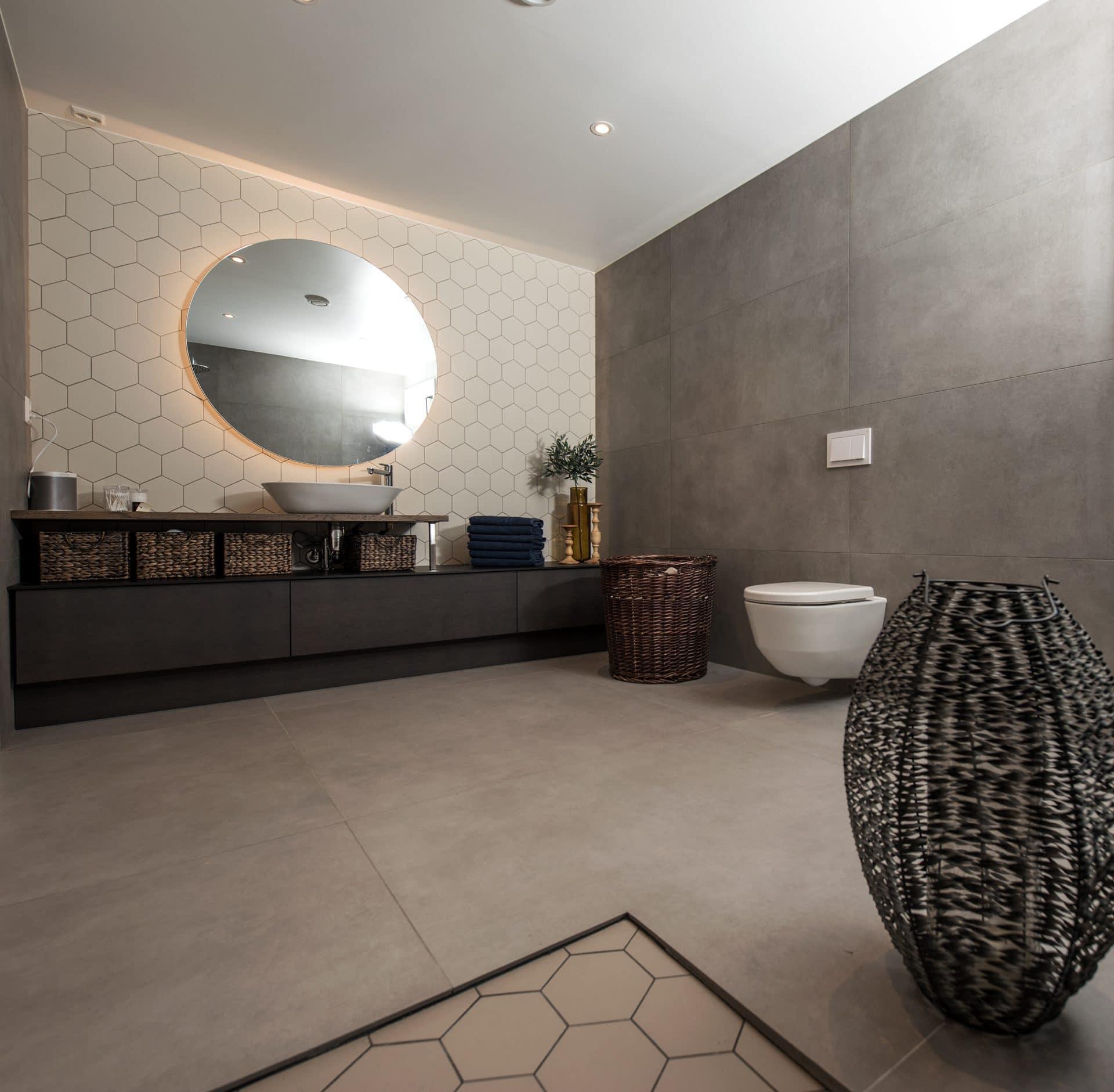 Moderne bad med sekskantede fliser og rundt speil