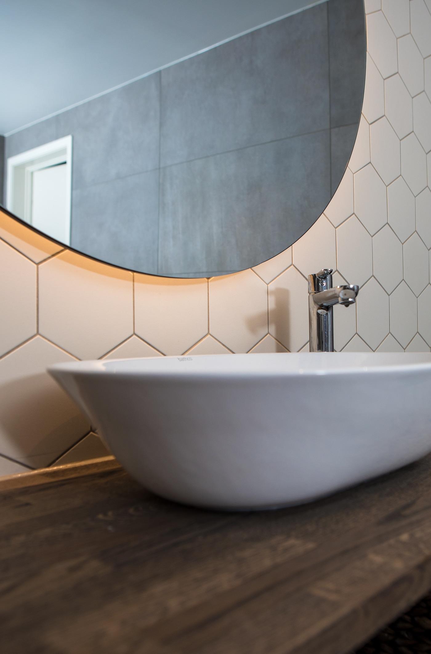 Detaljbilde fra bad med sekskantede fliser og rundt speil