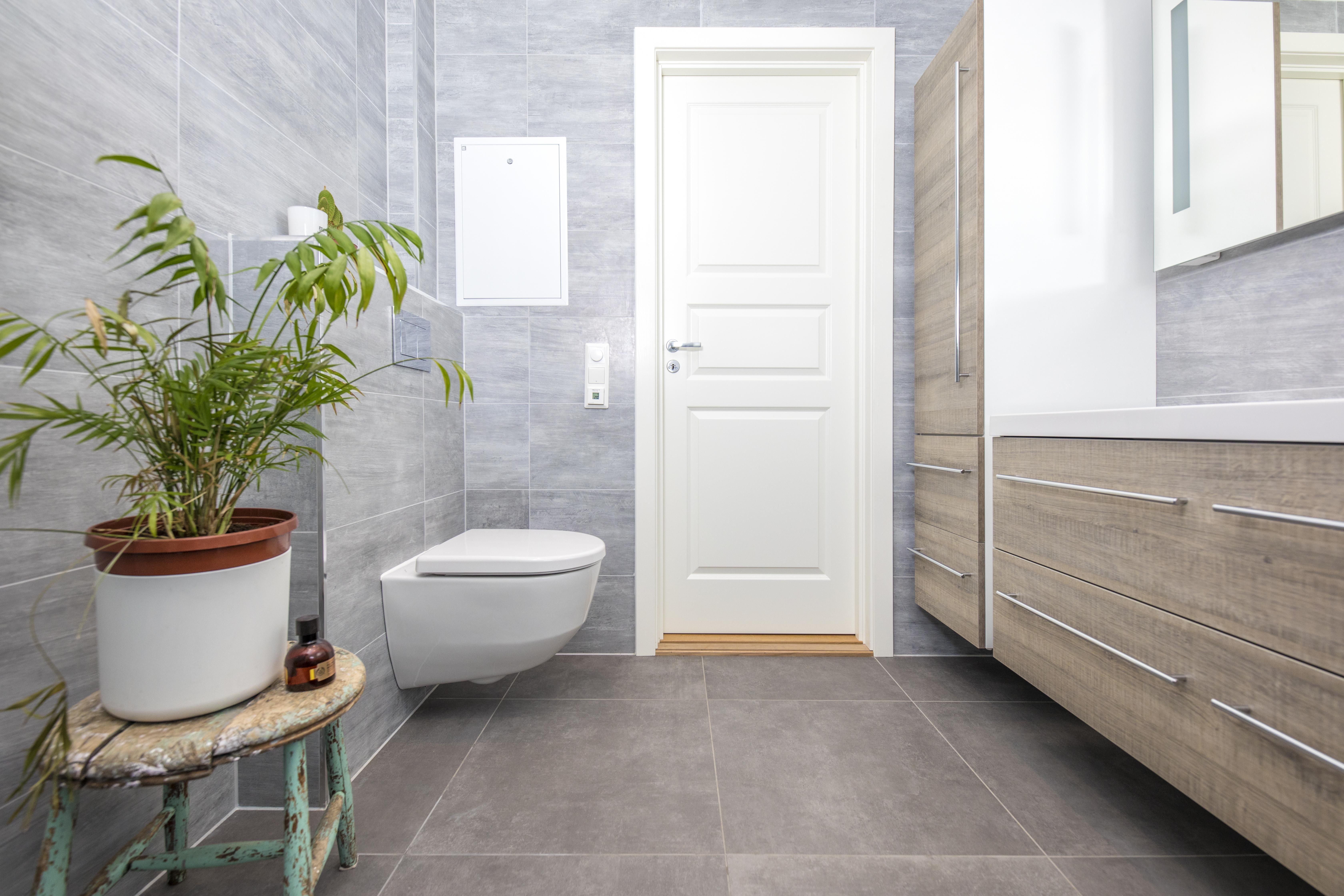 Nyoppusset grått og brunt bad med vegghengt toalett