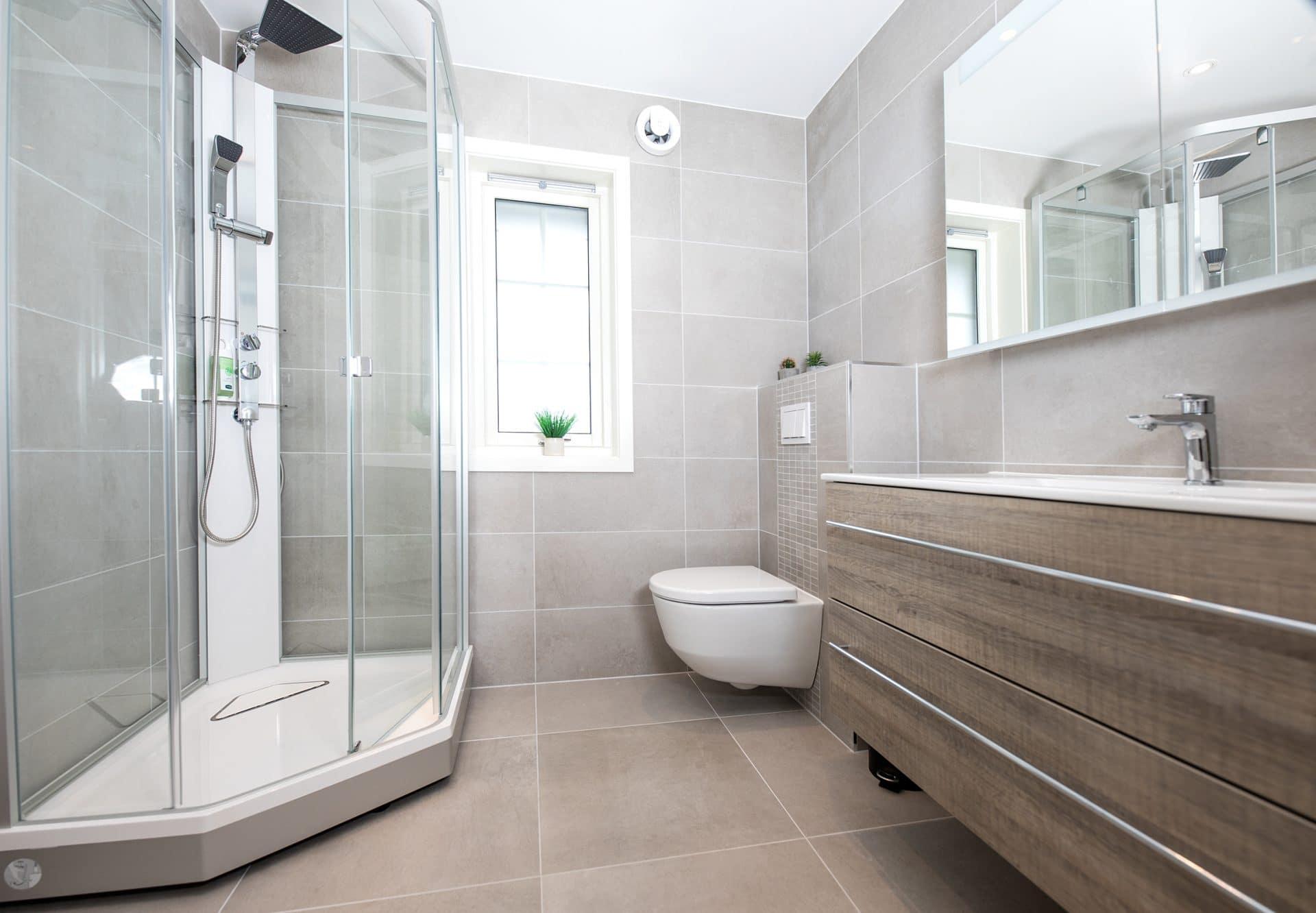 Nyoppusset bad med dusjkabinett og vegghengt toalett